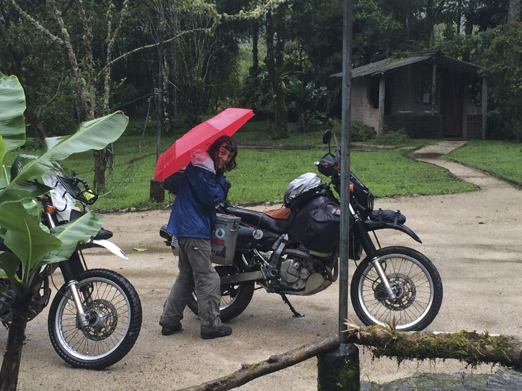 Shannon packing the bikes in the rain while Mike looks on from the covered porch. It is good we left that day because landslides have been plaguing the road out ever since.