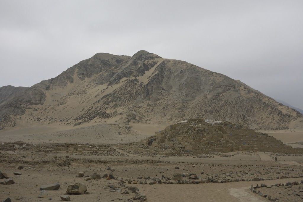 The smaller pile in front of the mountain is one of the pyramids at the Sacred City of Caral.