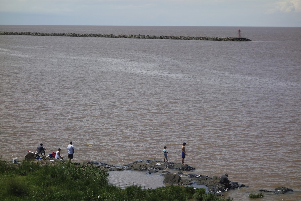 Fisherman on the Rio de la Plata. I have no idea what kind they were but these fellows had caught some monster fish that they kept alive in onion sacks submerged in the river. Colonia Del Sacramento, Uruguay.
