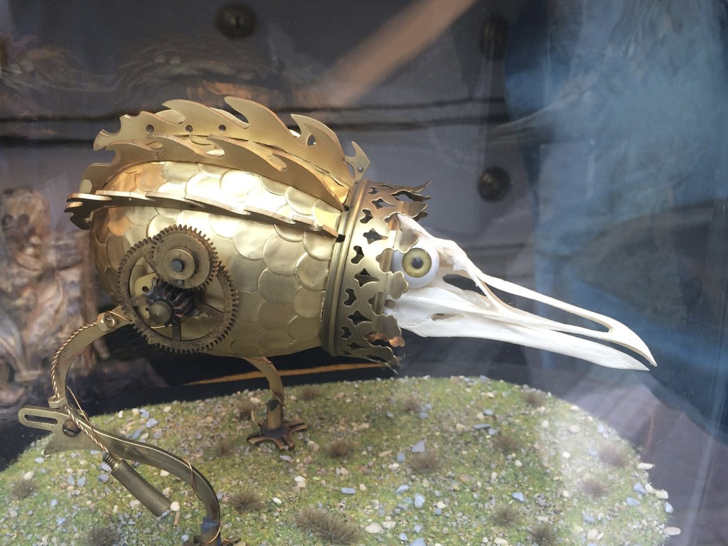 Steam punk bird peaking out of a shop window in Belgium.